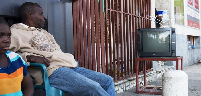 Men watch television in the street in Maputo. Photo © Timothy Haccius / Zitamar News