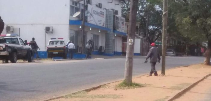 Police outside the Recheio supermarket in Pemba on 13 June, where armed attacks took the owner hostage. Photo: Ntatenda